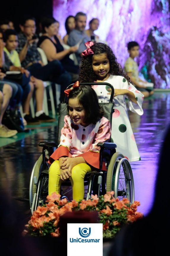 Na cadeira, a modelo mirim Ana Beatriz Zanim, de Marialva, exibe uma das criações de Karla Carraro em desfile promovido pelo Unicesumar, no TCC da então universitária