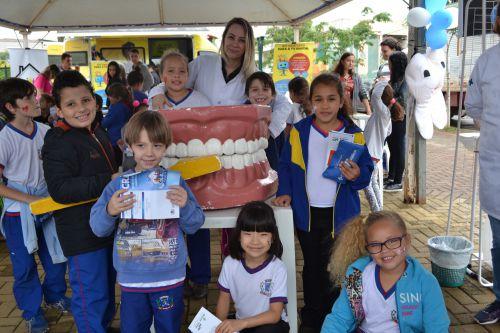 Coordenadora da Odontologia de Marialva, Valéria de Souza Ribeiro posa para foto com crianças presentes no evento