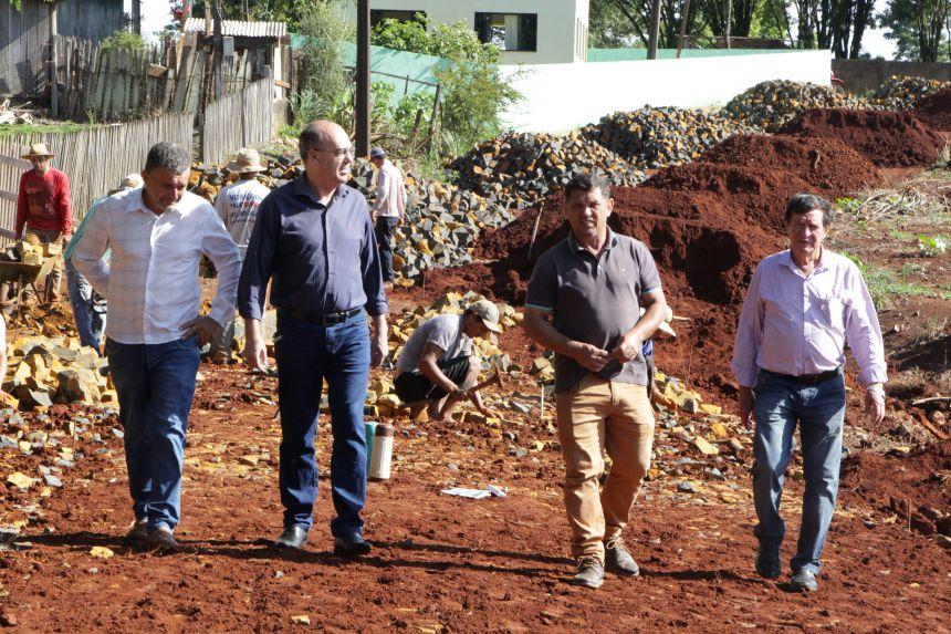 Antônio Carlos Brotti (empreiteiro da obra), Miguel Amaral, Ilson Gagliano e Adir Salla caminham pela obra de pedras irregulares
