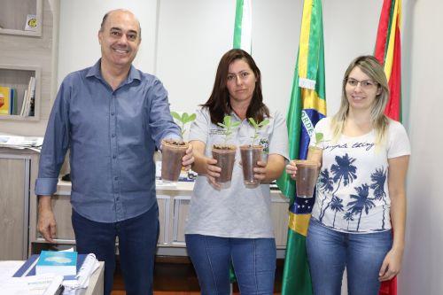 Prefeito Miguel Amaral, Mel Biancato e a bióloga Denise Kusminski exibem mudas de Crotalária