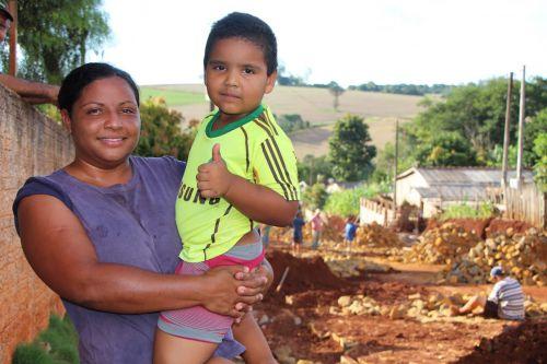 Marciana Mello, que também vive na Rua Mamborê, segura o filho Willian Lima e mostra obra