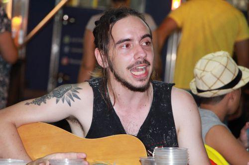 Gabriel Chambó (voz e violão) canta em espaço público