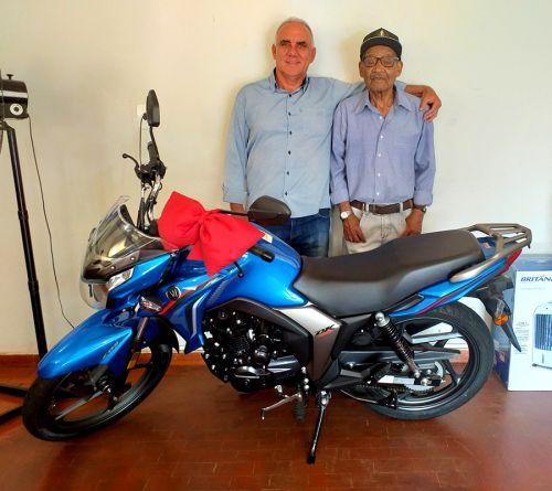Ganhador da moto 0km, Seu Arcângelo, de 94 anos, recebe seu prêmio das mãos do prefeito José Isalberti
