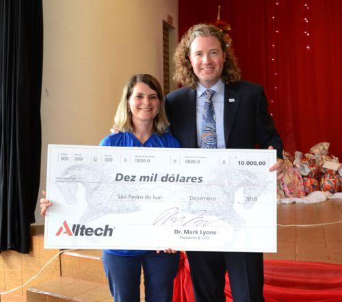CEO da Alltech Mark Lyons e coordenadora do CAIS/SCFV F�tima Amaral com cheque simb�lico