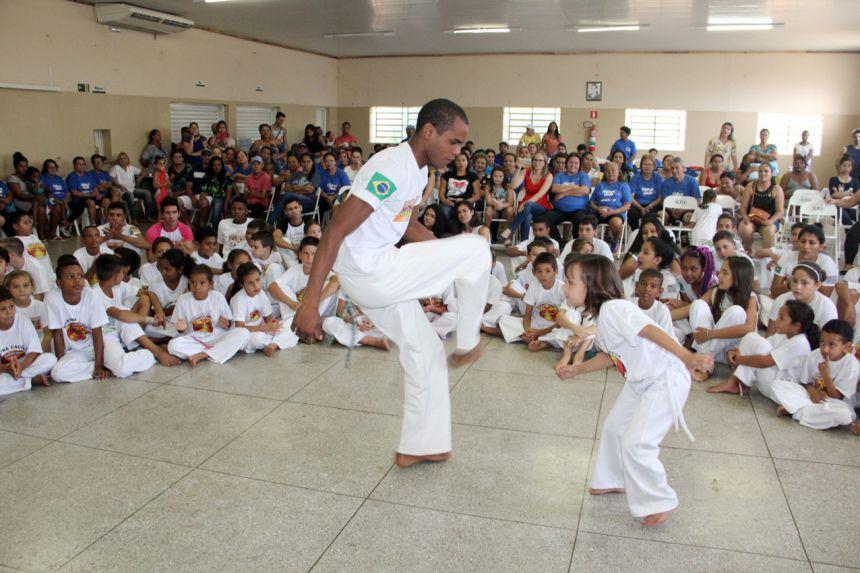 Aluna jogando capoeira com mestre