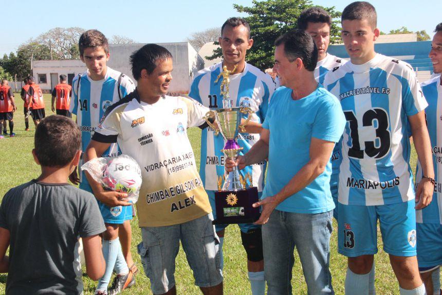 Técnico do Inacreditável Alexandre feliz ao receber o troféu do prefeito Val Dantas