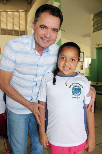 Prefeito Val Dantas e aluna da escola Nelson Magnani contente com o uniforme