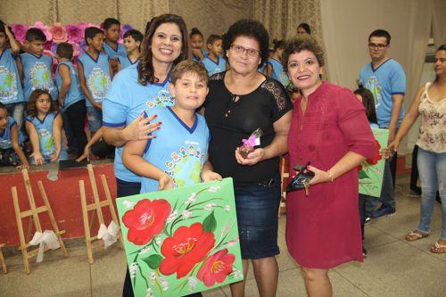 Primeira-dama Rose Barbosa e professora Clarice entregam quadro durante a homenagem