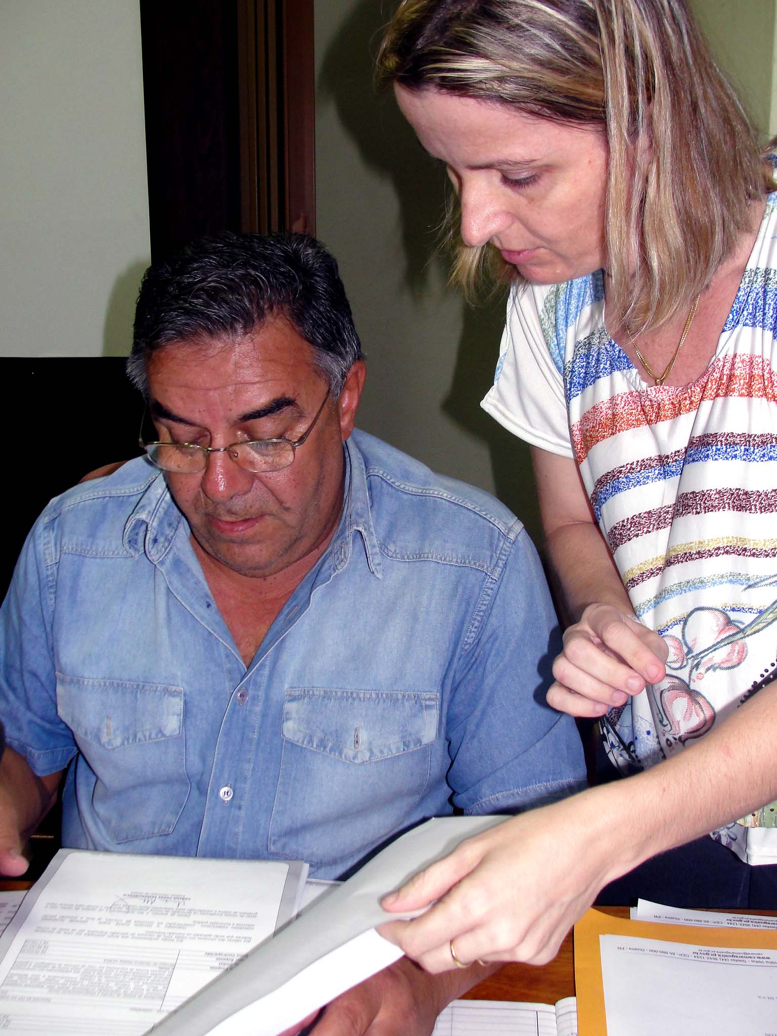 Secretário Getulio Benites Centurião e a oficial legislativo Adriana na preparação dos documentos da sessão.