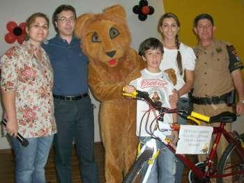 Vice-prefeito, policial Paulo Batista, mascote do Proerd e professoras entregaram a bicicleta para o aluno Danilo Silva, que elaborou uma redação sobre o programa