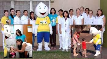 Secretária de Saúde, Tatiane Watanabe (ao centro) com Zé Gotinha e equipe de vacinação