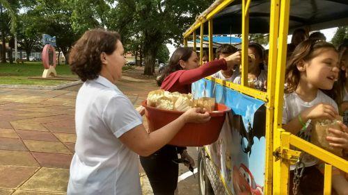Ao fundo, a primeira dama Joselene Gomes entrega pipoca aos estudantes.