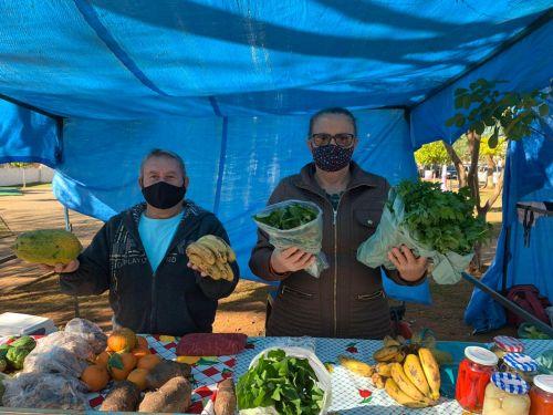 Casal de feirantes, diante da antiga barraca: frutas e verduras à venda